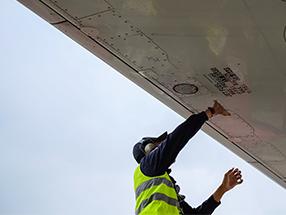 Ground handler performing aircraft visual check